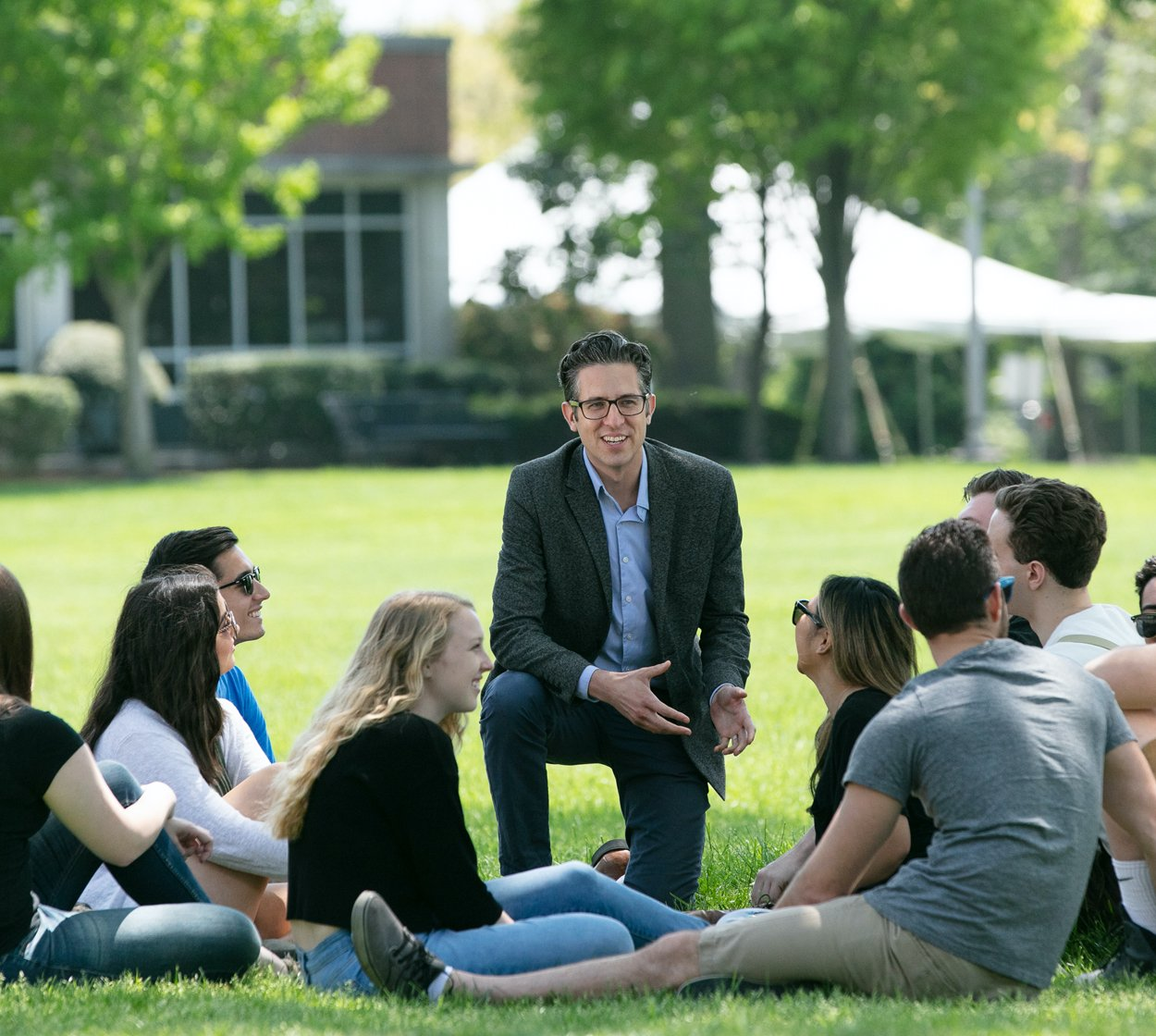 A professor lectures to a group of students outside.