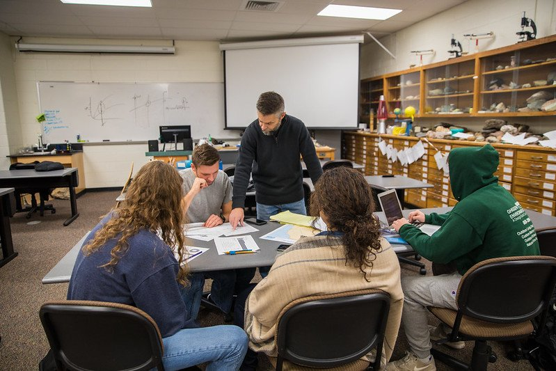A professor teaching to a table of students in a geology lab.