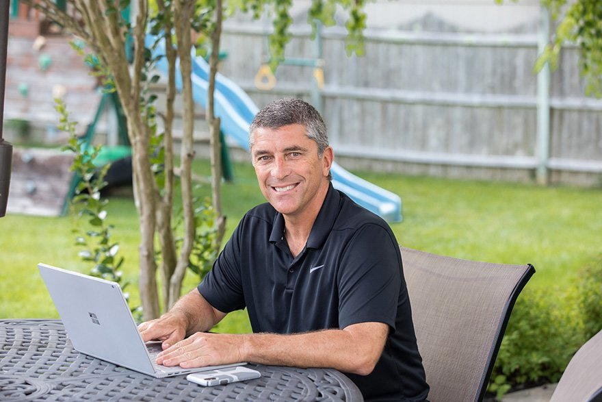a man smiles while working on his laptop outside