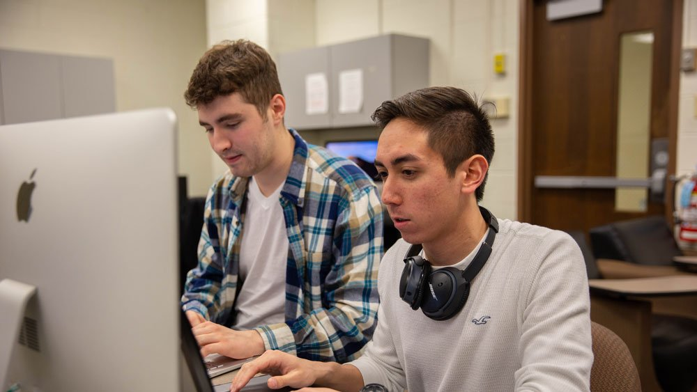 Two computer science students work in a lab.