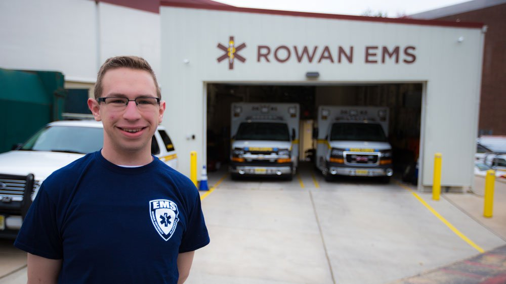 A student stands in front of Rowan's EMS department.