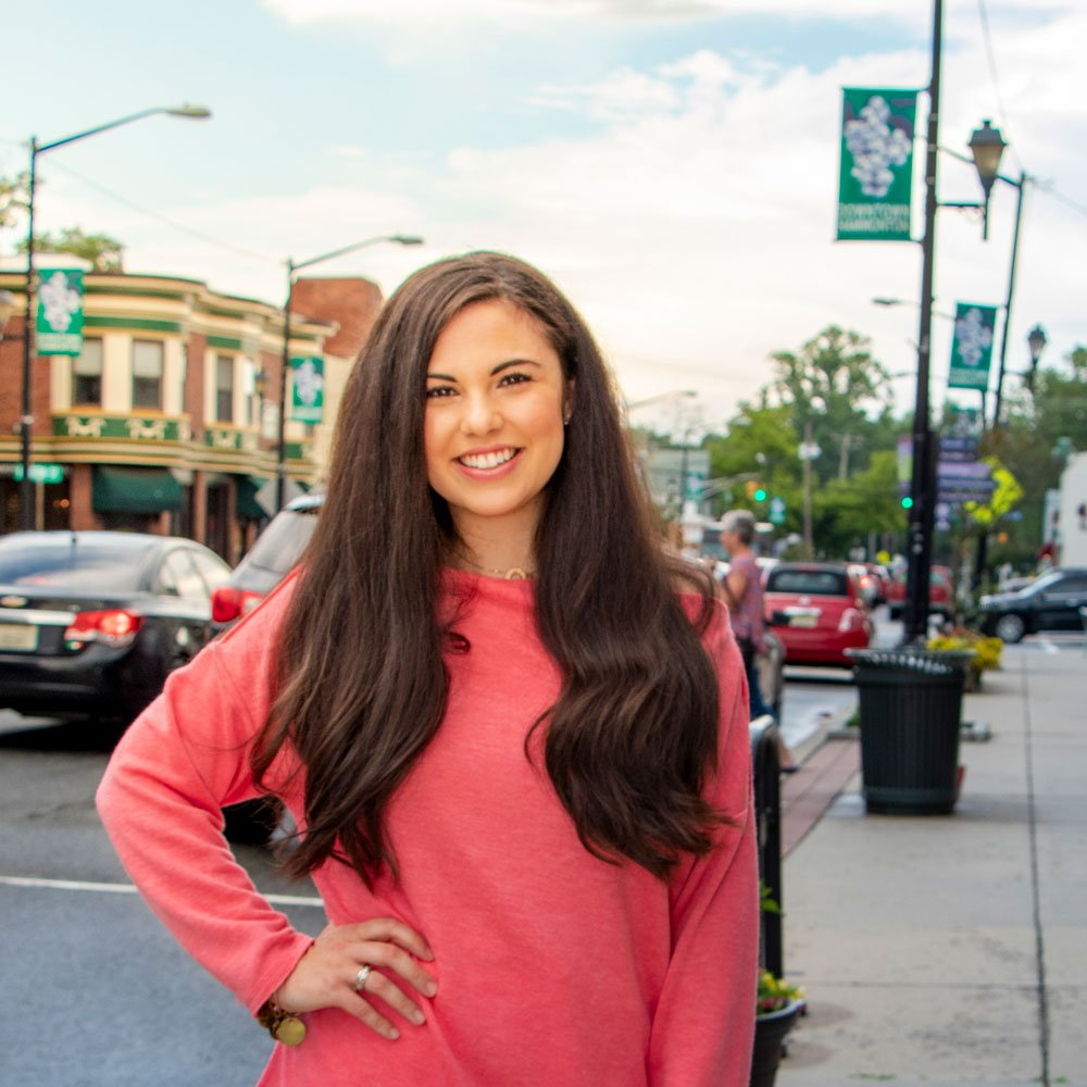 Christina D. stands in a downtown neighborhood