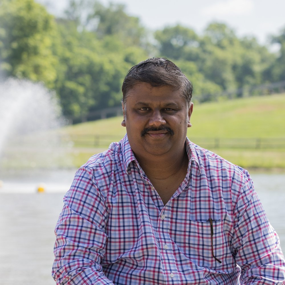Ganesh sits outside in front of a lake with a fountain